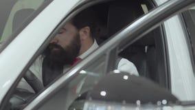 Zit de portret aantrekkelijke zekere gebaarde zakenman in het voertuig en inspecteert onlangs gekochte auto van de auto stock video