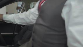 Zit de portret aantrekkelijke zekere gebaarde zakenman in het voertuig en inspecteert onlangs gekochte auto van de auto stock videobeelden