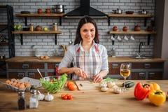 Zit de vrolijke vrouw van Nice bij lijst in keuken Zij die koken De vrouw kijkt op camera en glimlach Zij sneed groene ui op bure royalty-vrije stock foto