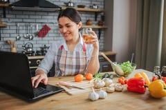 Zit de vrolijke vrouw van Nice bij lijst in keuken Zij typt op toetsenbordlaptop en glimlach Modelgreepglas witte wijn stock foto's