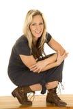 Zit de vrouwen donkere kleding laarzen en glimlach Royalty-vrije Stock Fotografie