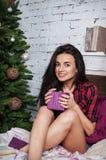 Zit het donker-haired meisje van Nice dichtbij Kerstboom met het heden in handen Het huis wordt verfraaid door vakantie Royalty-vrije Stock Foto
