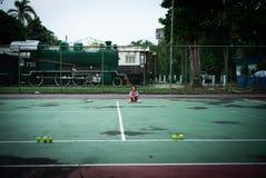 Zit het portret Aziatische meisje op de tennisbaan na hard het spelen stock fotografie