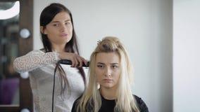 Zit het schrik nieuwe model op het haar bij de kapper, dat houdt het ijzer bij de wortel van het haar is om de krullen te maken d stock video