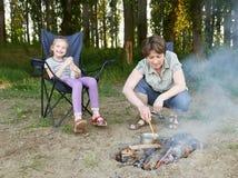 Zit het vrouwen kokende voedsel, mensen die in bos, familie kamperen actief in aard, kindmeisje in reiszetel, zomer Royalty-vrije Stock Foto's