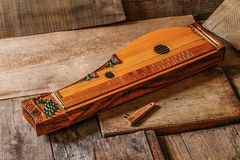 Zither - ancient folk instruments. Ancient stringed folk instrument made of wood Stock Images