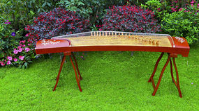 Zither, chinese traditional musical instrument. Zither, the traditional chinese musical instrument displayed in a spring garden Royalty Free Stock Photo