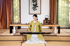 Zither performance-China tea ceremony. China woman show China tea ceremony in classical Chinese teahouse Royalty Free Stock Images