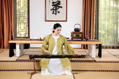Zither performance-China tea ceremony. China woman show China tea ceremony in classical Chinese teahouse Stock Image