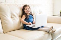 Zitieren Sie kleines Mädchen mit Laptop im Wohnzimmer Lizenzfreies Stockbild