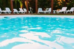Zitkamerstoelen dichtbij pool Stock Foto