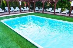 Zitkamerstoelen dichtbij pool Stock Afbeelding