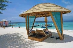 Zitkamerstoelen die door een bamboehut in de schaduw worden gesteld op het strand Stock Fotografie