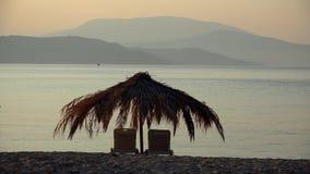 Zitkamerstoelen en palmparaplu op het strand, ontspannende vakantie in exotische toevlucht, kleurrijke zonsondergang met overzees stock videobeelden