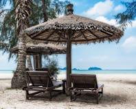 Zitkamerstoelen en zonneschermparaplu op het strand stock afbeeldingen