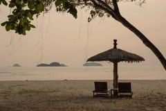 Zitkamerstoelen en zonneschermparaplu op het strand royalty-vrije stock afbeelding
