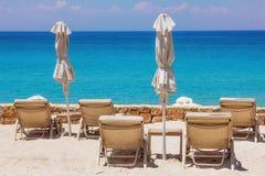 Zitkamerstoelen op het strand in Sani, Griekenland Stock Fotografie
