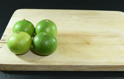 Zitrone auf Holzklotz auf schwarzem Hintergrund Lizenzfreie Stockfotos