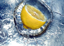 Zitrone, die Wasser spritzt lizenzfreie stockfotografie