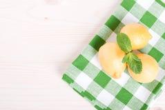 Zitrone drei mit tadellosem Blatt auf einer Tabelle auf eine klechatoy Oberseite der Serviette Lizenzfreies Stockbild