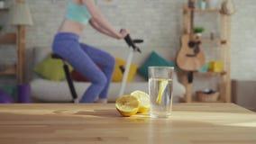 Zitrone fällt in ein Glas Wasser, im Hintergrund, den das Mädchen auf einem Standrad engagiert wird stock video footage