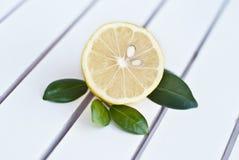 Zitrone halb mit grünen Blättern Lizenzfreie Stockfotografie