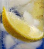 Zitrone-Keil im Glasmineralwasser mit Eis lizenzfreie stockbilder