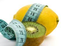 Zitrone, Kiwi und messendes Band Stockbilder