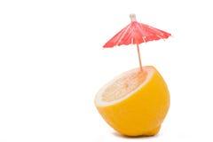 Zitrone mit einem Cocktailregenschirm Stockbild