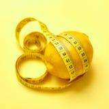 Zitrone mit messendem Band auf einem gelben Hintergrund Lizenzfreies Stockfoto