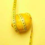 Zitrone mit messendem Band auf einem gelben Hintergrund Stockfotografie