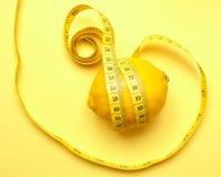 Zitrone mit messendem Band auf einem gelben Hintergrund Stockbilder