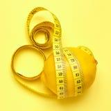 Zitrone mit messendem Band auf einem gelben Hintergrund Lizenzfreies Stockbild