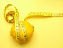Zitrone mit messendem Band auf einem gelben Hintergrund Lizenzfreie Stockfotografie