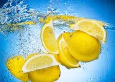 Zitrone-Scheiben, die unter Wasser mit Spritzen fallen Stockfoto