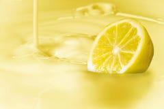 Zitrone tauchte in eine klare gelbe Flüssigkeit mit der Übereinstimmung von Milch ein Stockbild