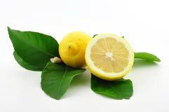 Zitrone und Zitrone halb mit Blättern Lizenzfreies Stockfoto