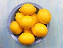 Zitronen auf einer blauen Platte auf einem blauen schäbigen Holztisch Stockbilder