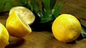 Zitronen mit Blättern auf hölzernen Brettern stock video footage