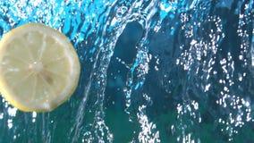 Zitronen-Scheiben-Fliegen durch die Wasser-Kaskade, die in der Zeitlupe bei fps 1500 spritzt stock video footage