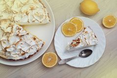 Zitronen-Törtchen mit Meringe Caramelized Creme auf Platte auf weißem hölzernem Hintergrund und einem Stück des Törtchens mit Zit Stockfotografie