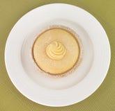 Zitronen-Torte, weiße Platte, grüner Hintergrund Lizenzfreies Stockbild