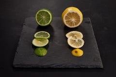 Zitronen- und Kalkscheiben auf Schneidebrett stockfoto
