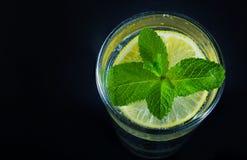 Zitronengetränk und -minze auf dem schwarzen Hintergrund Stockbild