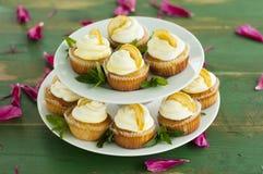 Zitronenkleine kuchen auf grünem Hintergrund Lizenzfreie Stockfotos