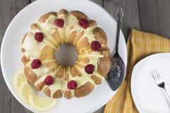 Zitronenkuchen bereift mit gelber Zuckerzuckerglasur und roten Himbeeren, Lizenzfreies Stockbild