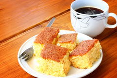 Zitronenkuchen und -Tasse Kaffee auf Holztisch Lizenzfreie Stockfotos