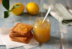 Zitronenmarmelade im Glasgefäß mit Frucht herum stockfoto