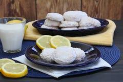 Zitronenplätzchen mit Puderzucker mit Zitronen und einem Glas von Mil Lizenzfreies Stockbild