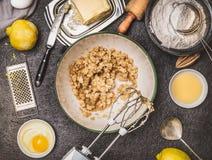 Zitronenplätzchen- oder -kuchenvorbereitung mit dem Kochen von Bestandteilen Butter und Zucker, die mit Handmischer auf dunklem K Lizenzfreie Stockbilder